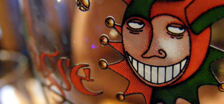 The Brugse Zot jester clown gremlin thing grimaces from a beer glass