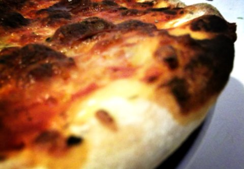 Pizza with floury burned crust.