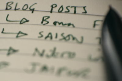 Coming up with content: writing lists in a notebook.