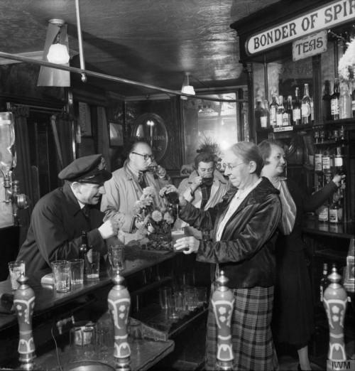 Bar scene: the landlady pours a bottled beer for a uniformed man.