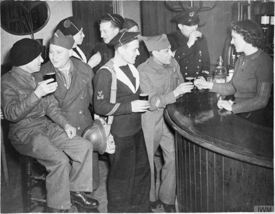 A mixed group of uniformed men and a barmaid.
