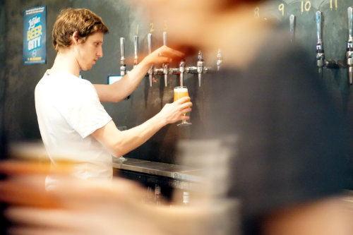 A barman pouring beer from a keg tap.