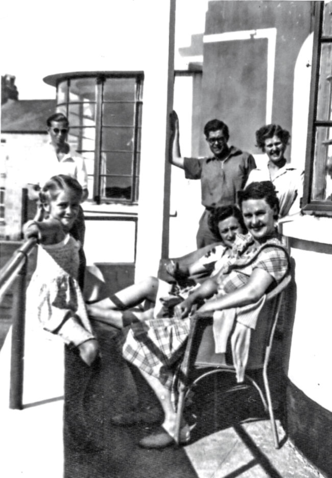 Family sits in blinding sun smiling at camera.