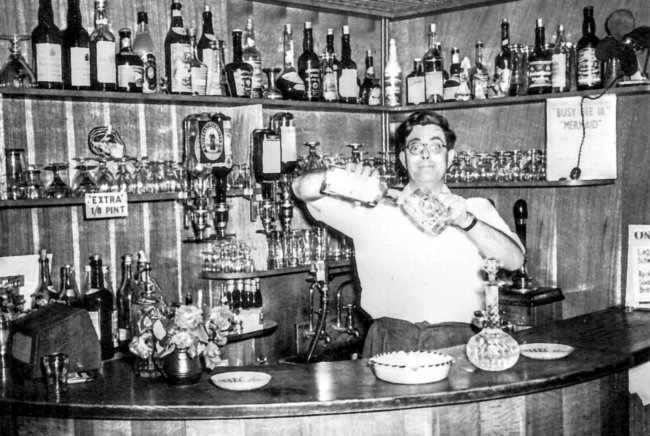 Bespectacled landlord pulling a funny face while pouring a cocktail.