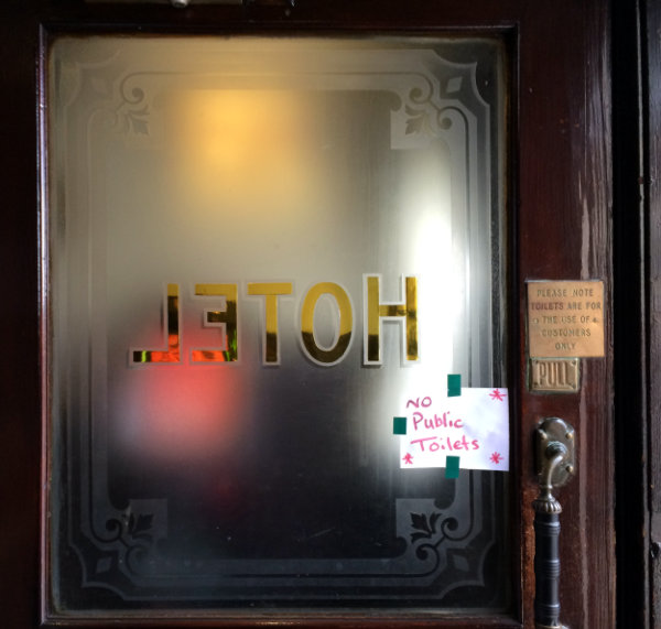Hotel sign painted on glass of pub inner door.