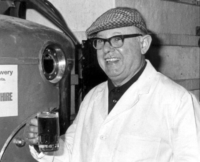 Urquhart in glasses and flat cap raising a pint.