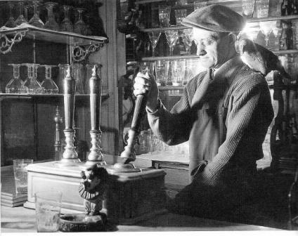 A man works handpumps in a Belgian estaminet.