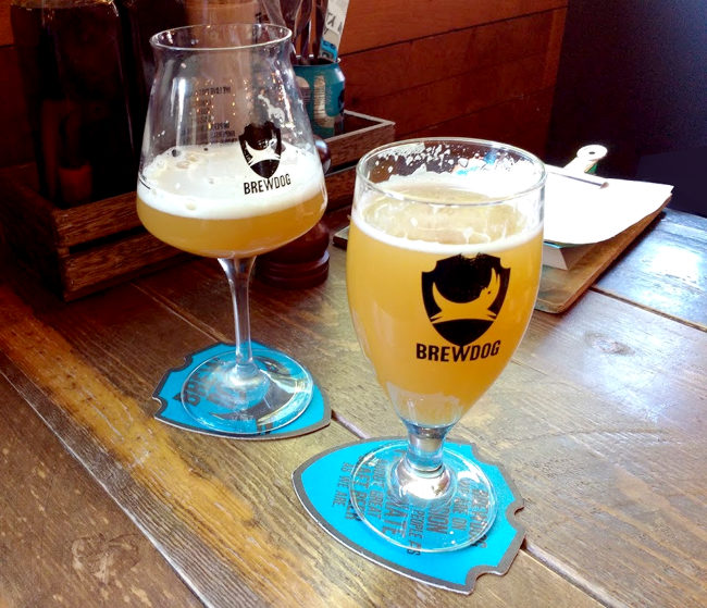 Two cloudy beers in fancy glasses.