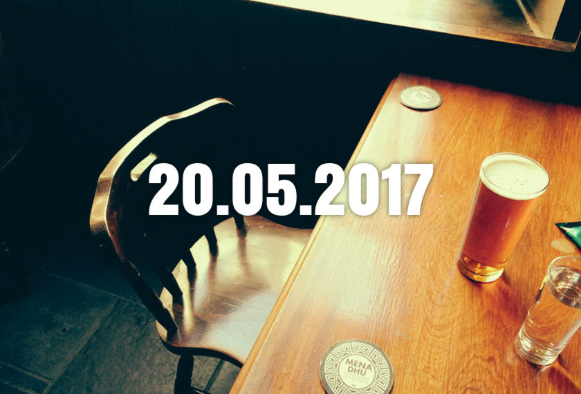 A chair, table and pint of beer in a basic pub.