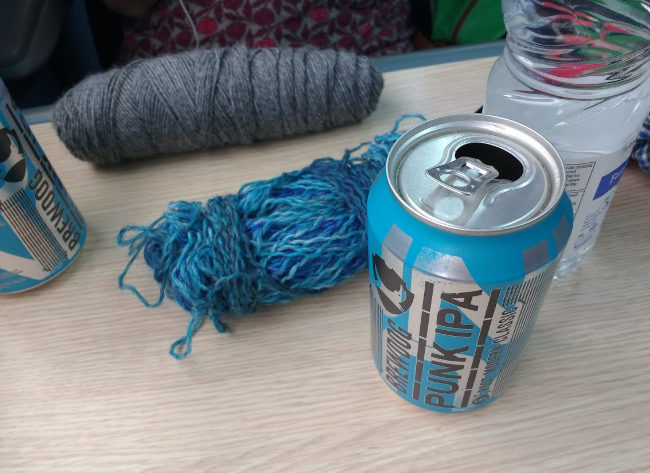 Cans of punk on a train table with wool.