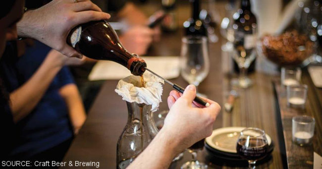 Beer being poured through a cheesecloth.