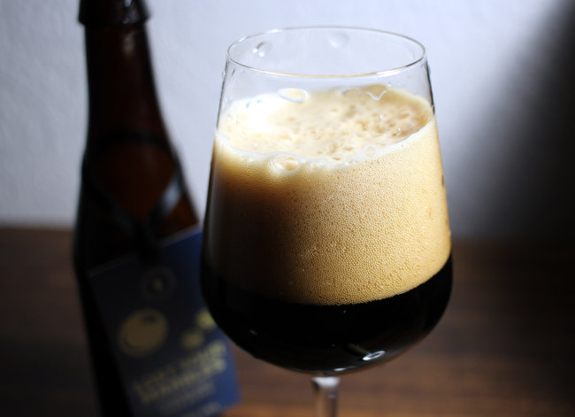 A dark old ale in the glass with bottle.