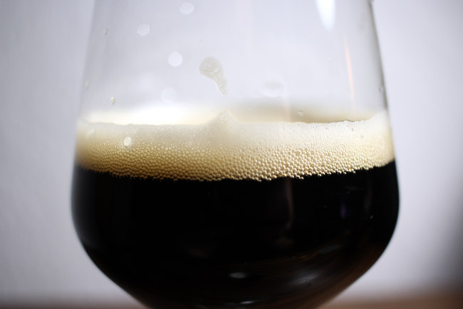The head of a glass of dark old ale.