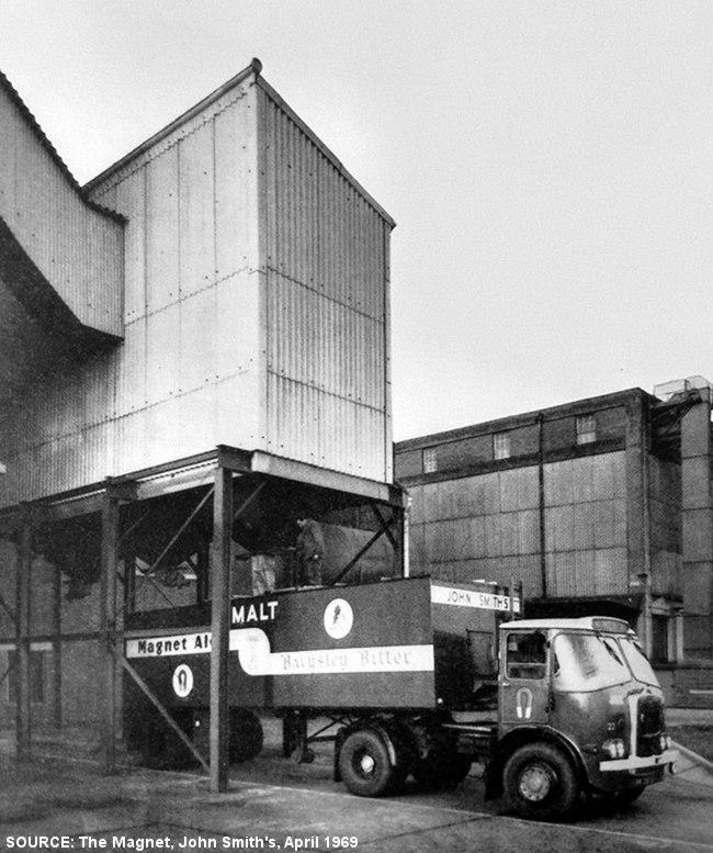 A truck beneath a silo.