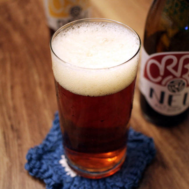 Altbier in a glass on a knitted beer mat.