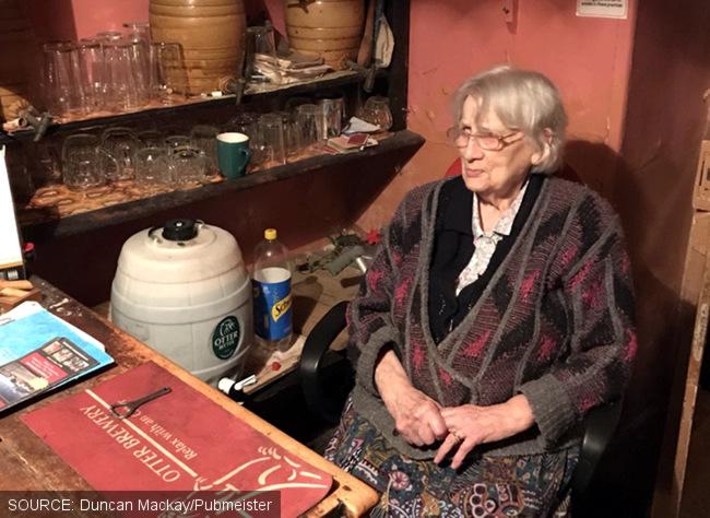 An elderly woman behind a small bar.