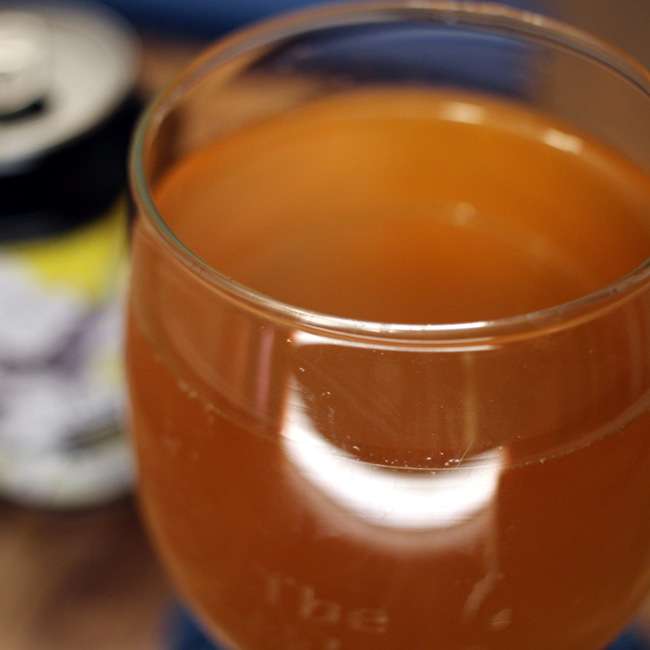 A glass of flat, orange beer.