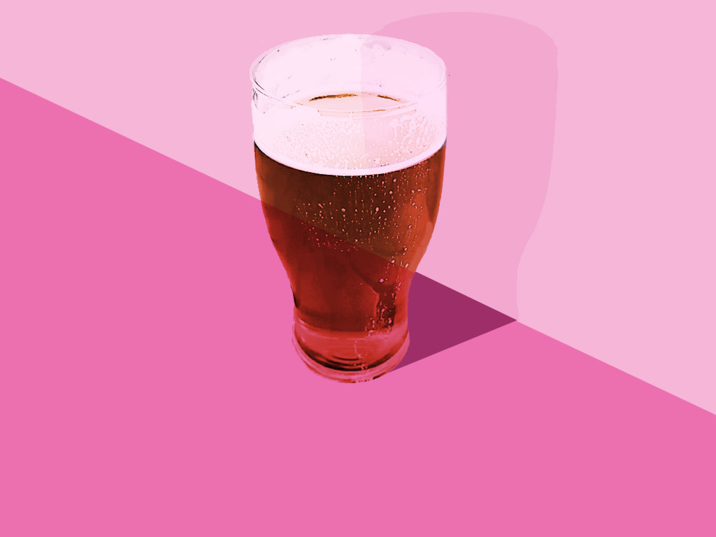 A pint of beer against pink.