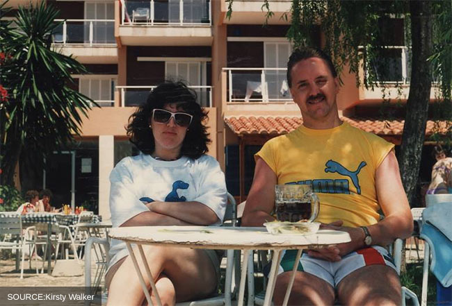 Vintage photo of a man and woman sitting in the sun with a pint of beer.