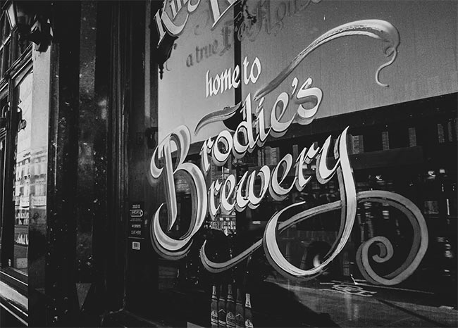 A painted sign advertising Brodie's Brewery on a pub window.