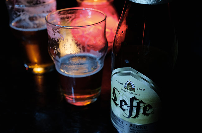 Half pint beer glasses and a bottle of Leffe.