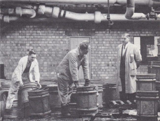 Men working with metal casks.