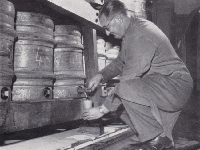 A man dispensing Guinness from a cask.