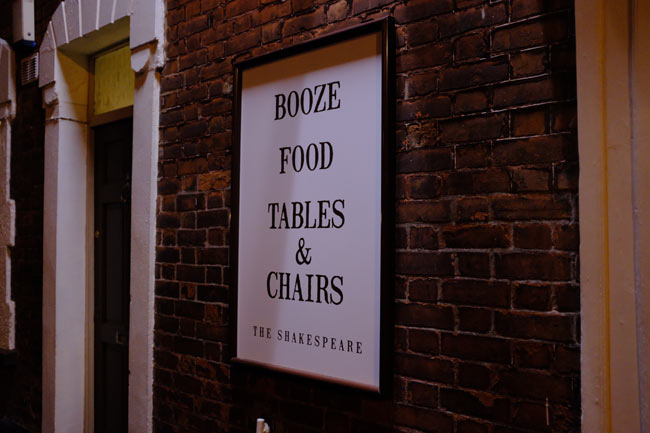 "Sign: ""Booze, food, tables & chairs""."